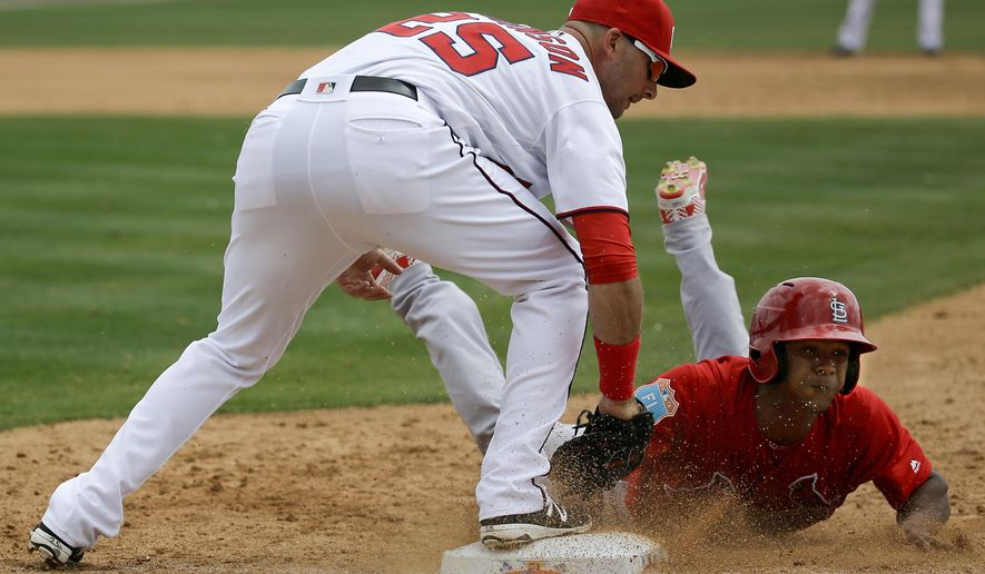 St. Louis Cardinals Magneuris Sierra, right, slides safely back to first base as Washington Nationals first baseman Clint Robinson, left, applies the tag in the third inning of a spring training baseball game, Sunday, March 13, 2016, in Viera, Fla. (AP Photo/John Raoux)