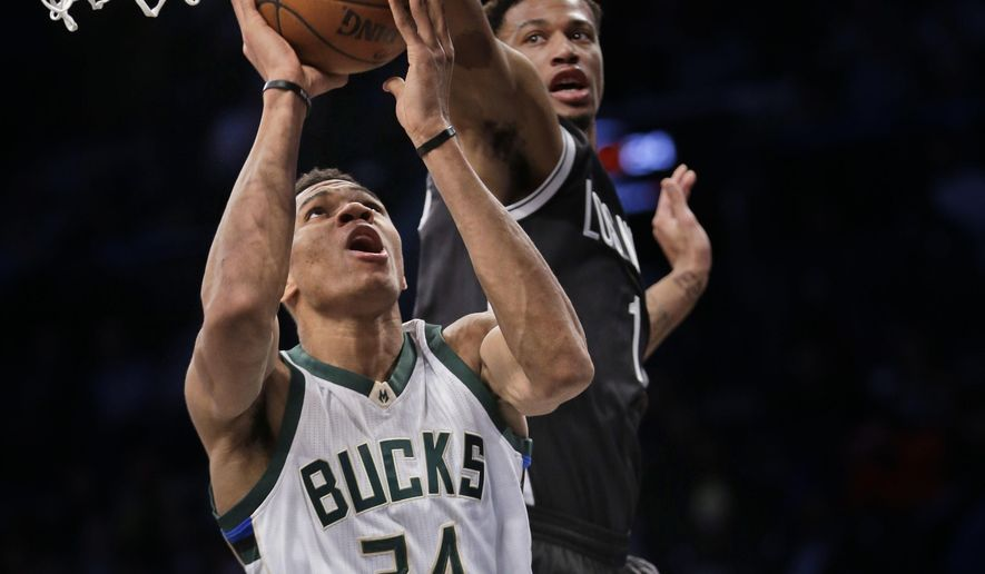 Milwaukee Bucks' Giannis Antetokounmpo, left, puts up a shot past Brooklyn Nets' Chris McCullough during the first half of the NBA basketball game at the Barclays Center, Sunday, March 13, 2016 in New York. (AP Photo/Seth Wenig)