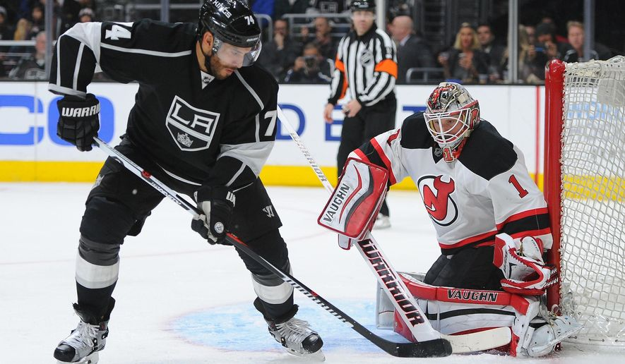 The Los Angeles Kings' Dwight King controls the puck in front of New Jersey Devils goalie Keith Kinkaid during the second period of an NHL hockey game in Los Angeles, Saturday, March 12, 2016. (AP Photo/Michael Owen Baker)