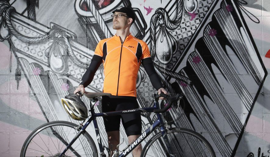 In this Feb. 23, 2016 photo, Shane Burry poses with his bicycle near the Moonshine mural by How and Nosm on Short Street in Lexington, Ky, Burry started taking photos on his iPhone of the places he stopped, specifically, photos of his bike in those charming sites. He then posted them to Facebook and Instagram, where he has more than 1,300 followers, usually adding an observation or an uplifting quote or two. (Pablo Alcala/Lexington Herald-Leader via AP) MANDATORY CREDIT