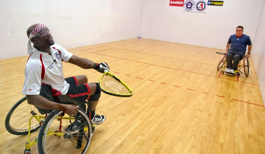 Steven Harper, left, with the Military Racquetball Federation plays a game with Harlon Matthews with Henry County Parks and Recreation at Robins Air Force Base, Ga., on  March 9, 2016. Harper helps run a adaptive sports fundamentals clinic at the base.   (Jason Vorhees/The Macon Telegraph via AP) MANDATORY CREDIT