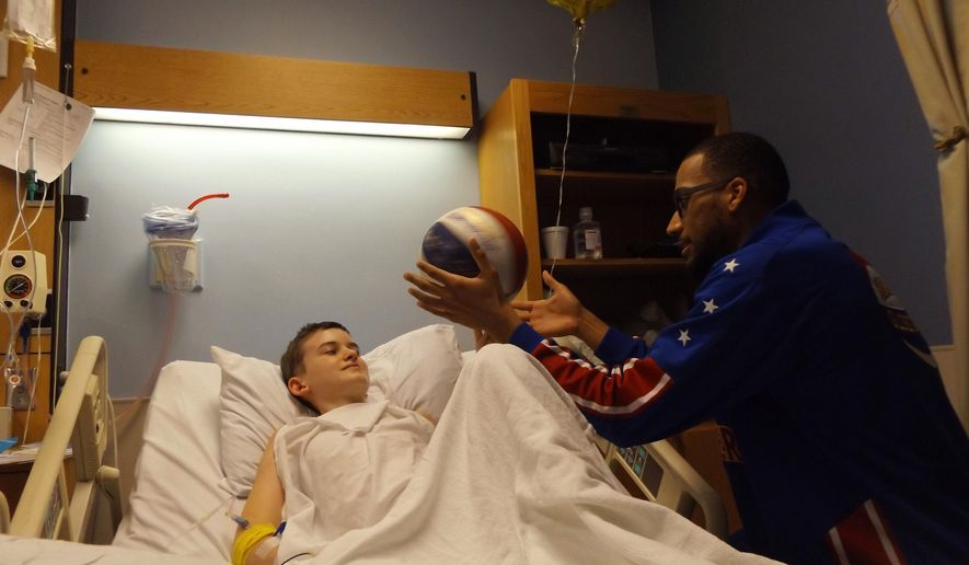ADVANCE FOR WEEKEND EDITIONS - In this Wednesday, March 9, 2016 photo, Harlem Globetrotter Zeus McClurkin visits with a sick patient at the children's wing at Holston Valley Medical Center in Kingsport, Tenn. McClurkin was in Kingsport as part of the Great Assist initiative, which pledges to spread 100 million smiles around the world over the next 10 years with acts of kindness. (Nick Shepherd/The Kingsport Times-News via AP) MANDATORY CREDIT