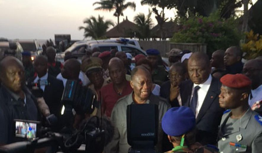 Ivory Coast's President Alassane Ouattara, center, visits the area were gunmen attacked people in Grand Bassam, Ivory Coast, March 13, 2016. At least six armed men attacked beachgoers outside three hotels Sunday in Grand-Bassam, killing several civilians and special forces, sending tourists fleeing through the historic Ivory Coast resort town. (AP Photo/Christin Roby )