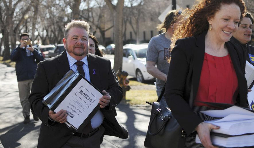 FILE - In this Feb. 23, 2016, file photo, Terri Bruce, left, a transgender man who opposed a bill that South Dakota Gov. Dennis Daugaard vetoed that would have limited the bathrooms that transgender students could use, walks toward the state Capitol in Pierre. Lawmakers considered several bills this session related to transgender people, none of which passed. (AP Photo/James Nord, File)