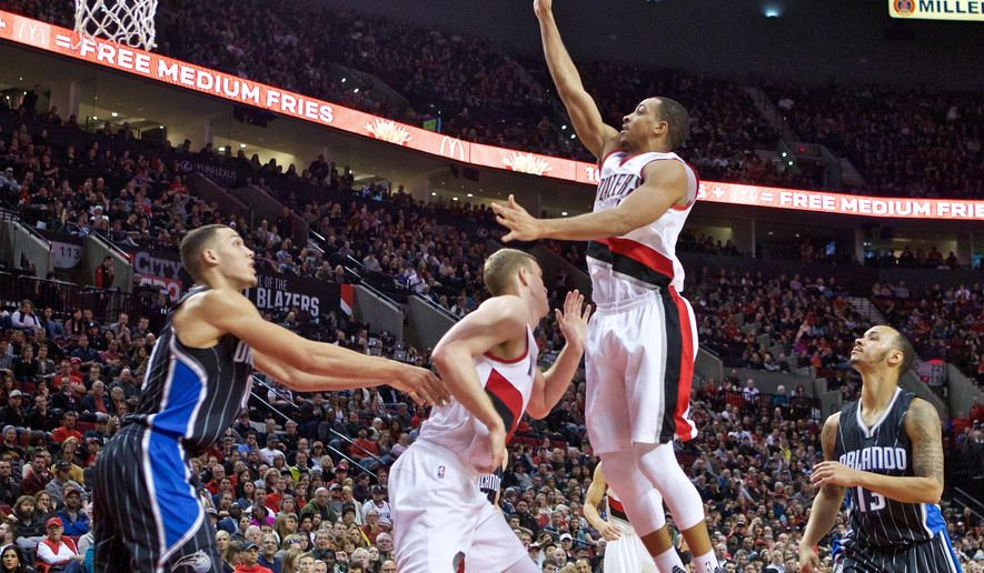 Portland Trail Blazers guard C.J. McCollum, center, shoots over Orlando Magic forward Aaron Gordon, left, and guard Shabazz Napier, right, during the second half of an NBA basketball game in Portland, Ore., Saturday, March 12, 2016. (AP Photo/Craig Mitchelldyer)