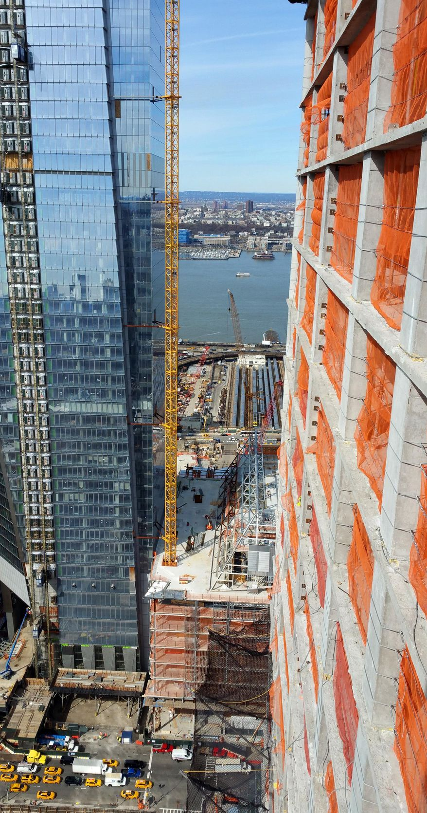This March 3, 2016, photo, from a high-rise under construction shows the view from the narrow walkway crane operators use to reach their glass control cab, on New York's west side. All around New York City, mammoth cranes fill the city skyline, erecting dozens of skyscrapers that are part of the city's current building boom. At right is Brookfield Property Group's Manhattan West project where orange netting is all that separates workers from a 50 floor drop. (AP Photo/Verena Dobnik)