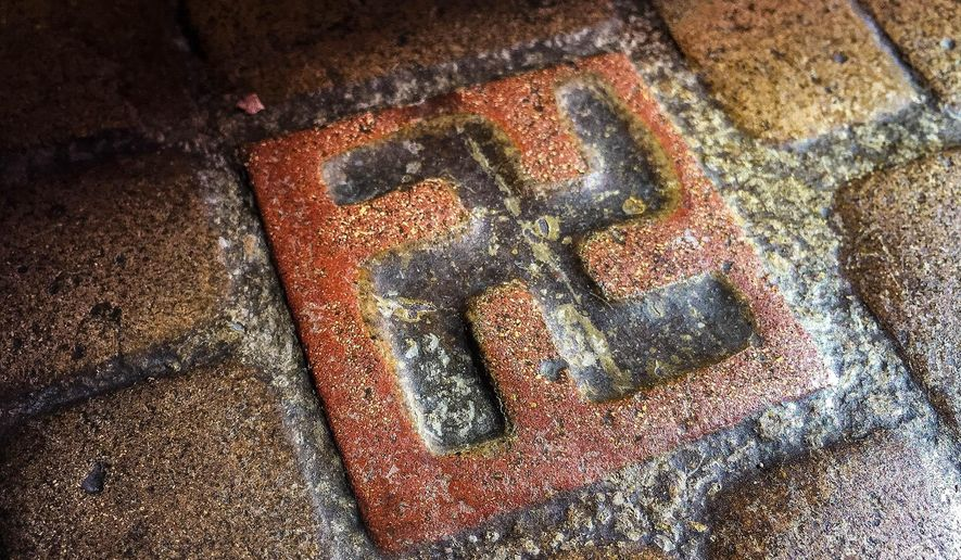 ADVANCE FOR WEEKEND EDITIONS - This March 3, 2016 photo shows one of about 60 floor tiles emblazoned with swastika-style crosses in the entrance to the Longview Community Church in Longview, Wash.  A Longview church established in 1925 bears tiles with symbols that were once seen as a sign of good fortune, but are now more closely associated with terror. (Marissa Luck/The Daily News via AP) MANDATORY CREDIT