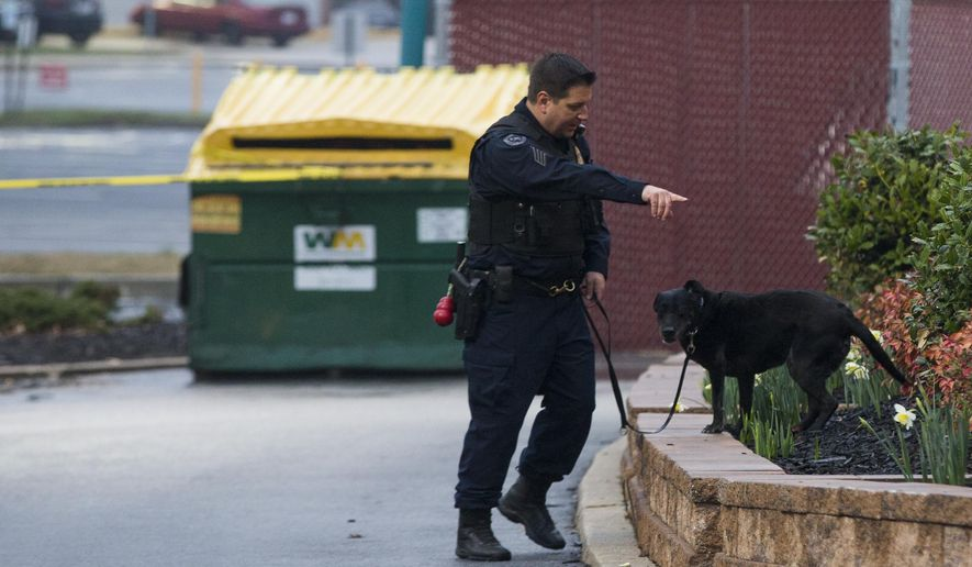 A police K9 unit searches the grounds of a Popeyes restaurant during an investigation into the shooting of a Prince George's County police officer outside a police station, on Sunday, March 13, 2016, in Hyattsville, Md. (AP Photo/Evan Vucci)