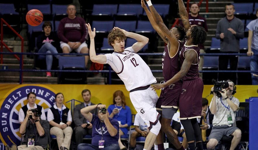 Arkansas Little Rock forward Lis Shoshi (12) loses control of the ball after a block from Louisiana Monroe forward DeMondre Harvey, right, and forward Jamaal Samuel, center, in the first half of an NCAA college basketball game in the championship of the Sun Belt Conference men's tournament in New Orleans, Sunday, March 13, 2016. (AP Photo/Max Becherer)