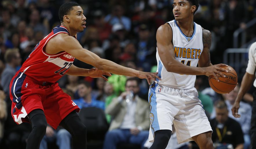 Denver Nuggets guard Gary Harris, right, looks to pass the ball as Washington Wizards forward Otto Porter Jr. defends in the first half of an NBA basketball game Saturday, March 12, 2016, in Denver. (AP Photo/David Zalubowski)