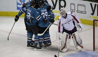 The San Jose Sharks celebrate a goal by Joe Pavelski next to Washington Capitals goalie Philipp Grubauer during the third period of an NHL hockey game Saturday, March 12, 2016, in San Jose, Calif. San Jose won 5-2. (AP Photo/Marcio Jose Sanchez)