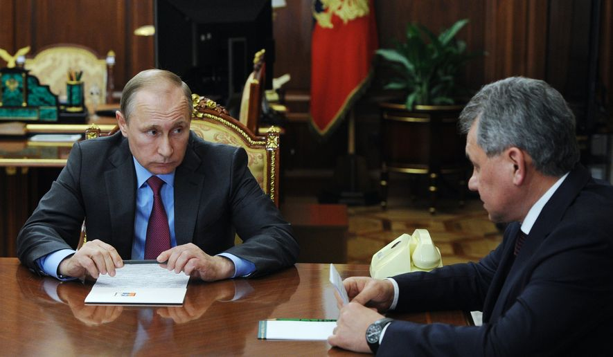 Russian President Vladimir Putin, left, listens to Russian Defense Minister Sergey Shoygu during their meeting in the Kremlin in Moscow, Russia, Monday, March 14, 2016. Russian President Vladimir Putin has ordered the start of the pullout of the Russian military from Syria starting Tuesday. (Mikhail Klimentyev, Sputnik, Kremlin Pool Photo via AP)