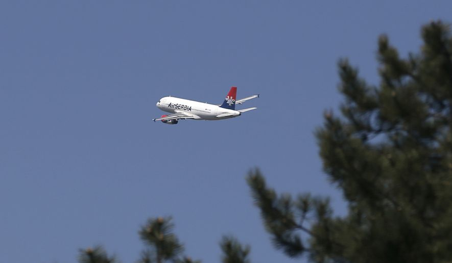 In this file photo taken Wednesday, April 15, 2015, an Air Serbia passenger plane flies over Belgrade, Serbia. Serbia's authorities are investigating reports that a cargo package bound for the United States containing two missiles with explosive warheads was found on a passenger flight from Lebanon to Serbia. (AP Photo/Darko Vojinovic)