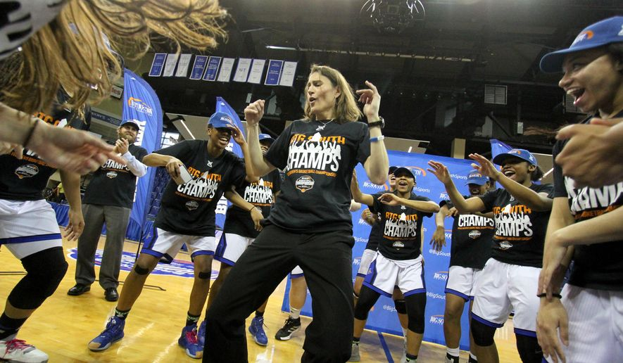 UNC Asheville's head coach Brenda Mock Kirkpatrick, center, and her team celebrate after winning the championship game of the NCAA women's Big South college basketball tournament in Asheville, N.C., against Liberty University on Sunday, March 13, 2016. (AP Photo/Ben Earp)