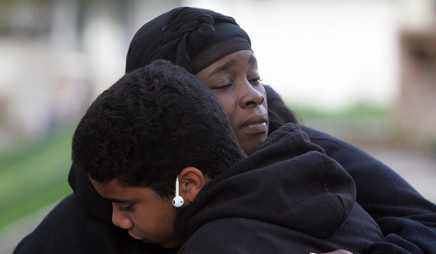 Kevin Estrada, 13, of San Bernardino, consoles Shaunte Spears, mother of Terrance Spears, 14, and aunt of Jason Spears, 12, who where shot overnight while walking to get chips at a nearby convenient store in San Bernardino, Calif., on Monday, March 14, 2016. Terrance was injured and Jason died from his wounds. Kevin was friends with the boys.  (Stan Lim/The Press-Enterprise via AP) MANDATORY CREDIT