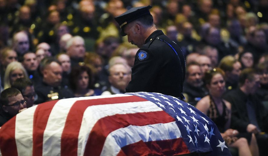 A Denver police officer stands watch over the flag draped casket at the memorial service for Park County Deputy Corporal Nate Carrigan at Faith Bible Chapel in Arvada, Colo., Monday, March 14, 2016. About 4,000 people filled the church Monday in suburban Denver to honor the sheriff's deputy who was shot and killed while trying to evict a man in the small Colorado mountain community where they both lived. (Helen H. Richardson/The Denver Post via AP) MANDATORY CREDIT