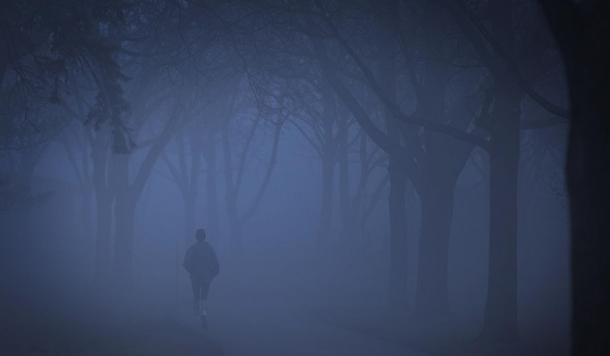 A runner disappears into the fog that blanketed the shores of Lake Nokomis in Minneapolis in the early morning on Monday, March 14, 2016. (Leila Navidi/Star Tribune via AP)  MANDATORY CREDIT; ST. PAUL PIONEER PRESS OUT; MAGS OUT; TWIN CITIES LOCAL TELEVISION OUT