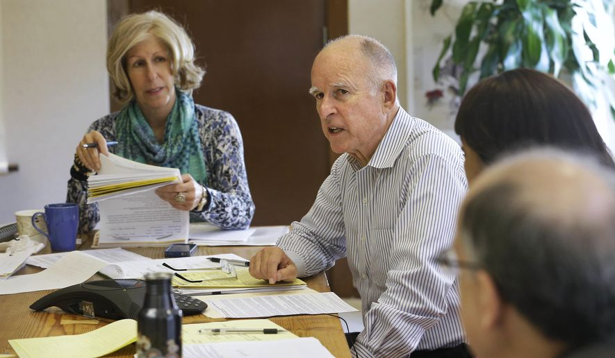 In this Sept. 29, 2014, file photo Gov. Jerry Brown meets with his executive secretary Nancy McFadden, left, and other advisors at his Capitol office in Sacramento, Calif. The advocacy group Consumer Watchdog said Monday, March 14, 2016, that it has asked the Fair Political Practices Commission to investigate whether McFadden had a conflict of interest because of her stock holding in her former employer, Pacific Gas & Electric. (AP Photo/Rich Pedroncelli)