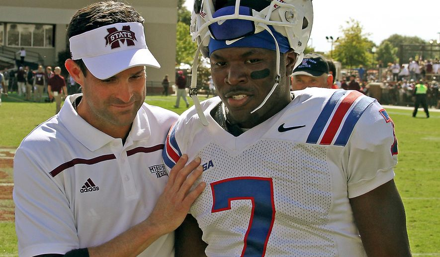 FILE - In this Oct. 17, 2015, file photo, then-Mississippi State defensive coordinator Manny Diaz, left,  speaks with Louisiana Tech safety Xavier Woods (7) after their NCAA college football game in Starkville, Miss. The Miami Hurricanes' new defensive coordinator understands the enormity of the job that awaits starting Tuesday, March 15, 2016,when Miami opens spring practice for the first time under new head coach Mark Richt and a revamped staff. (AP Photo/Jim Lytle, File)