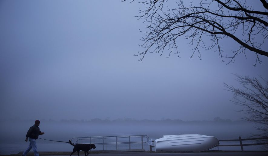 A man walks his dog at Lake Nokomis in Minneapolis in the early morning on Monday, March 14, 2016, as dense fog blanketed the metro area Monday morning.(Leila Navidi/Star Tribune via AP)  MANDATORY CREDIT; ST. PAUL PIONEER PRESS OUT; MAGS OUT; TWIN CITIES LOCAL TELEVISION OUT