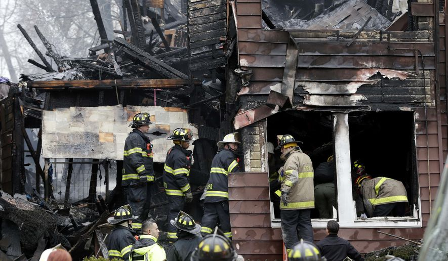 Firefighters look through the wreckage of a house destroyed by a fire in Orange, N.J., Monday, March 14, 2016. (AP Photo/Seth Wenig)