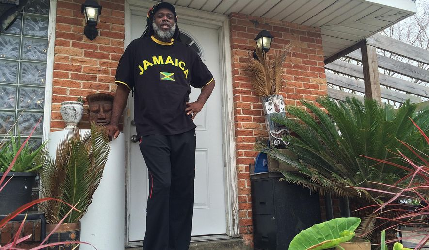 In this March 10, 2016 photo, Baba Ken Amen, an artist and vegan caterer, poses for a photo at his home in Pontchartrain Park in New Orleans. Amen says he makes ends meet renting his art-filled, solar-powered home on Airbnb. (AP Photo/Cain Burdeau)