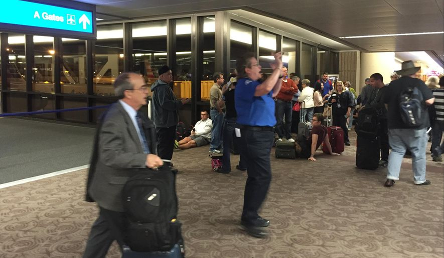 This Monday, March 14, 2016 photo provided by passenger Matt Cowan shows people being evacuated at Sky Harbor International Airport in Phoenix. A security checkpoint at Sky Harbor International Airport in Phoenix has reopened after a police bomb squad was summoned to check out an item that produced a suspicious X-ray image. Transportation Security Administration spokesman Michael England says the bomb squad checked the item and determined it wasn't explosive. Airport spokeswoman Julie Rodriguez says the closure lasted about an hour Monday morning. (Matt Cowan via AP)