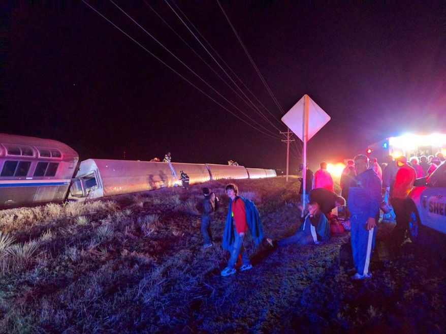 Passengers gather after a train derailed near Dodge City, Kan., Monday, March 14, 2016. An Amtrak statement says the train was traveling from Los Angeles to Chicago early Monday when it derailed just after midnight. (Daniel Szczerba via AP)