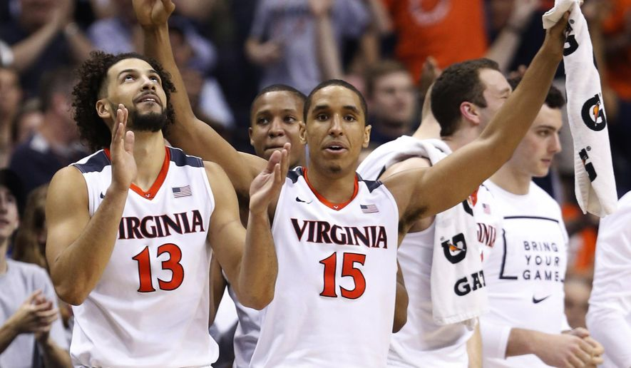 FILE - In this March 10, 2016, file photo, Virginia guard Malcolm Brogdon (15) and forward Anthony Gill (13) cheer their team during the second half against Georgia Tech in an NCAA college basketball game in the Atlantic Coast Conference men's tournament, in Washington. Seniors Brogdon and Gill have been at the forefront of one of the most successful periods in Virginia's men's basketball history. They would like to finish with a deep run in the NCAA Tournament, starting with their game against Hampton. (AP Photo/Steve Helber, File)