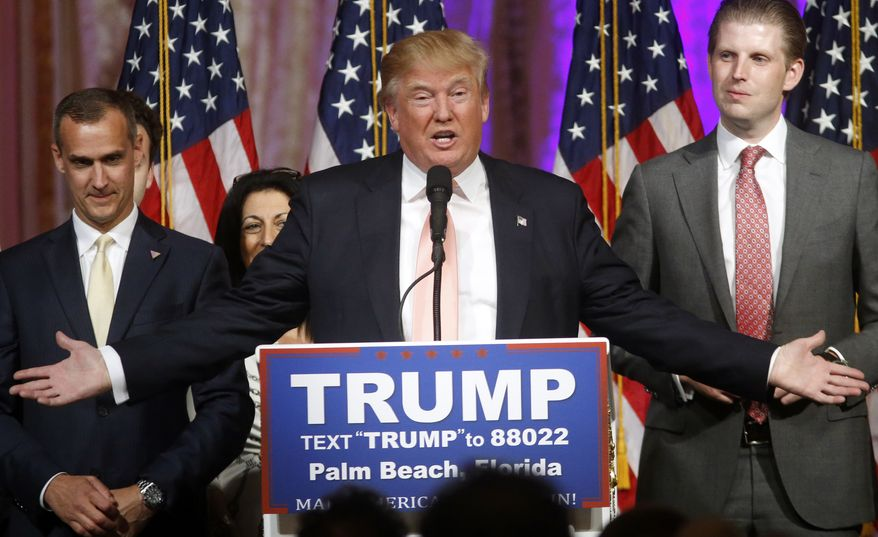 Republican presidential candidate Donald Trump speaks to supporters at his primary election night event at his Mar-a-Lago Club in Palm Beach, Fla., Tuesday, March 15, 2016. At right is his son Eric Trump and at left is campaign manager Corey Lewandowski. (AP Photo/Gerald Herbert)