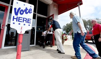 Voters walk into the Destin Community Center, Tuesday March 15, 2016, in Destin, Fla. Voters in Florida, as well as North Carolina, Illinois, Missouri and Ohio are casting their ballots in primary elections Tuesday. (Nick Tomecek/Northwest Florida Daily News via AP)