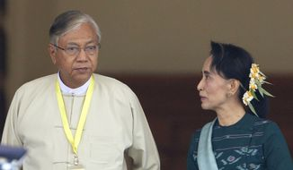Htin Kyaw, left, newly elected president of Myanmar, walks with National League for Democracy leader Aung San Suu Kyi, right, at Myanmar's parliament in Naypyitaw, Myanmar, Tuesday, March 15, 2016. Myanmar's parliament elected Htin Kyaw as Myanmar's new president Tuesday, a watershed moment that ushers the longtime opposition party of Aung San Suu Kyi into government. (AP Photo/Aung Shine Oo)