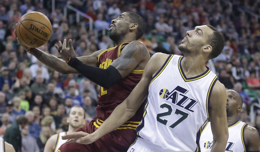 Cleveland Cavaliers guard Kyrie Irving, left, shoots as Utah Jazz center Rudy Gobert (27) defends during the second quarter of an NBA basketball game Tuesday, March 15, 2016, in Salt Lake City. (AP Photo/Rick Bowmer)