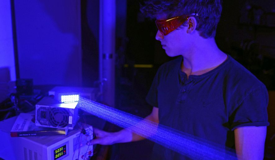"In this Feb. 26, 2016 photo, Drake Anthony, a senior at Southern Illinois University in Carbondale, demonstrates a blue laser diode bank. Anthony, also known as ""styropyro"" or ""The DIY Laser Guy,"" has turned his laser passion into a veritable YouTube empire. He has about 241,000 followers on YouTube of his videos. (Byron Hetzler/The Southern via AP)  MANDATORY CREDIT"