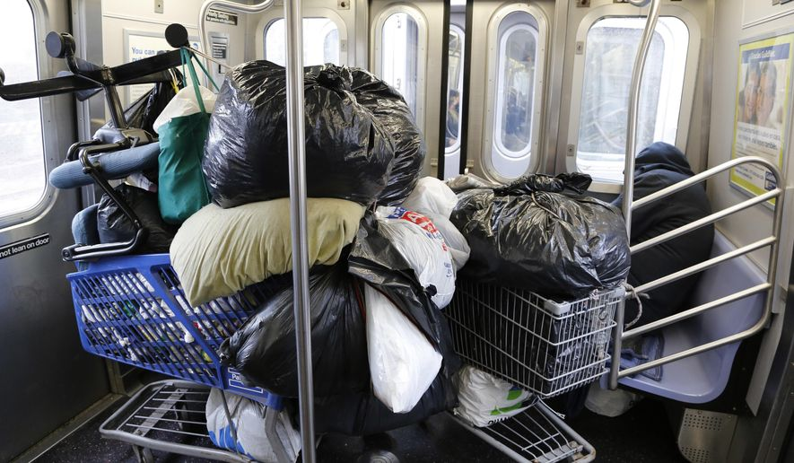 In this March 14, 2016 photo, a homeless man, right, sleeps with his belongings stacked into two shopping carts while riding the subway in New York.  Violence, both physical attacks as well as serious threats of bodily harm, is undoubtedly the major deterrent preventing our most marginalized neighbors from accessing lifesaving shelter, said Mary Brosnahan, president and CEO of the Coalition for the Homeless. (AP Photo/Mark Lennihan)