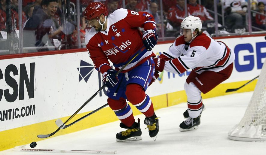 Washington Capitals left wing Alex Ovechkin (8), from Russia, prepares to get the puck over a broken stick with Carolina Hurricanes defenseman Noah Hanifin (5) behind him, in the first period of an NHL hockey game, Tuesday, March 15, 2016, in Washington. (AP Photo/Alex Brandon)