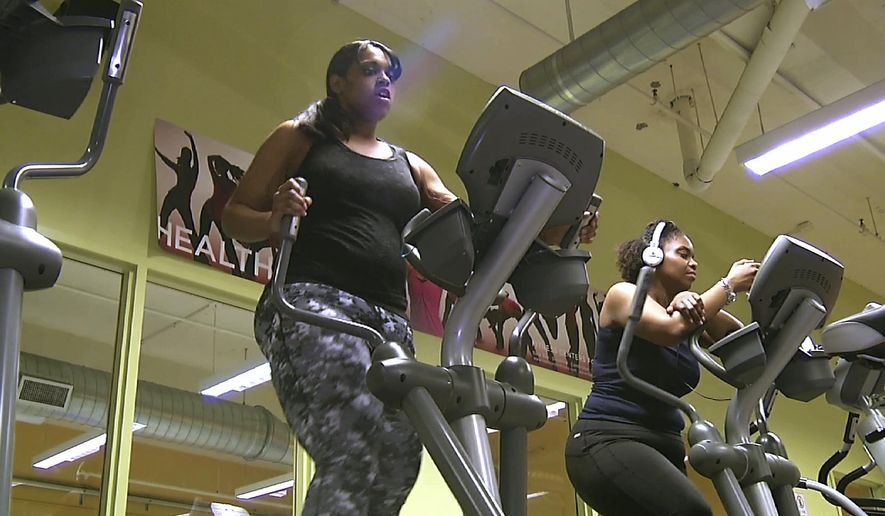 In this Feb. 1, 2016 still photo from video, Monisha Long, left, works on a elliptical machine in Boston's Dorchester neighborhood. Doctors treating chronic health problems increasingly are prescribing exercise instead of medicines for their patients. At one health center in Boston, primary care physicians, internists and psychologists prescribe access to a gym for $10 a month. (AP Photo/Rodrique Ngowi)