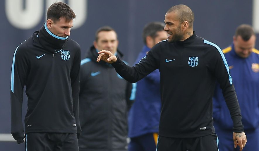 FC Barcelona's Lionel Messi, left, talks with his teammate Dani Alves during a training session at the Sports Center FC Barcelona Joan Gamper in San Joan Despi, Spain, Tuesday, March 15, 2016.  FC Barcelona will play against Arsenal in a Champions League Group E soccer match on Wednesday March 16. (AP Photo/Manu Fernandez)