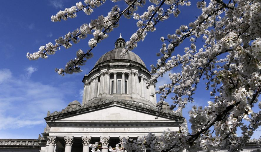 The Washington state Capitol is seen through cherry blossom trees, on Monday, March 14, 2016, in Olympia, Wash. (AP Photo/Rachel La Corte)