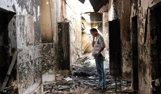 FILE - In this Oct. 16, 2015, file photo, an employee of Doctors Without Borders walks inside the charred remains of the organization's hospital after it was hit by a U.S. airstrike in Kunduz, Afghanistan. More than a dozen U.S. military personnel have been disciplined but face no criminal charges for mistakes that led to the bombing of a Doctors Without Borders hospital in Afghanistan last year that killed 42 Afghans, U.S. defense officials say. (AP Photo/Najim Rahim, File)