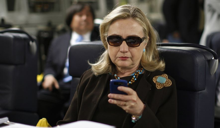 In this Oct. 18, 2011, file photo, then-Secretary of State Hillary Rodham Clinton checks her Blackberry from a desk inside a C-17 military plane upon her departure from Malta, in the Mediterranean Sea, bound for Tripoli, Libya. Newly released emails show a 2009 request to issue a secure government smartphone to then-Secretary of State Hillary Clinton was denied by the National Security Agency. (AP Photo/Kevin Lamarque, Pool, File)