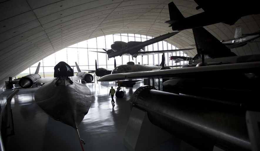A man walks through aircrafts and other items on display during a media event to mark the reopening of the American Air Museum after it underwent a major redevelopment, at the Imperial War Museum of aviation in Duxford, England, Wednesday, March 16, 2016. The transformed American Air Museum opens to the public from Saturday March 19 and tells the story of Anglo-American collaboration in 20th and 21st century conflict as seen through the eyes of the people linked with the aircraft and objects on display. (AP Photo/Matt Dunham)