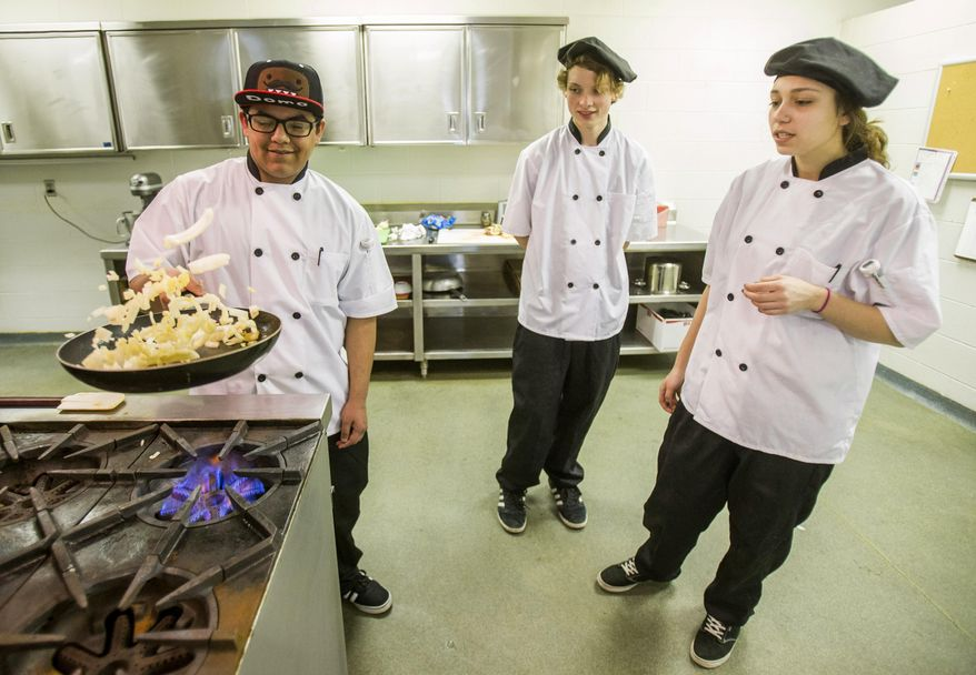 In this Thursday, March 9, 2016 photo, The Crossing students Brandon Reyes, left, Silas Bolen, center, and Julia Orr prepare food during a culinary class in South Bend, Ind. (Robert Franklin/South Bend Tribune via AP) MANDATORY CREDIT