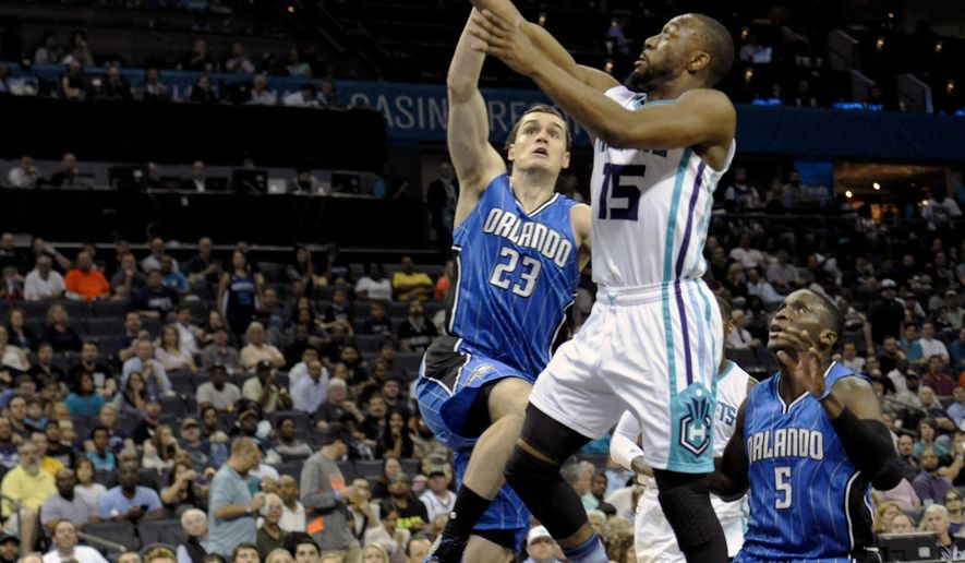 Charlotte Hornets guard Kemba Walker (15) shoots against Orlando Magic guard Mario Hezonja (23) during the first half of an NBA basketball game in Charlotte, N.C., Wednesday, March 16, 2016. (AP Photo/Mike McCarn)