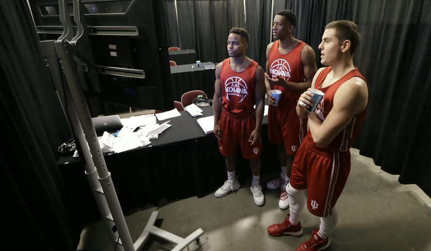 Indiana's Yogi Ferrell, from left, Troy Williams and Nick Zeisloft watch television as they wait to practice ahead of a first round men's college basketball game in the NCAA Tournament, Wednesday, March 16, 2016, in Des Moines, Iowa. Indiana will play Chattanooga on Thursday. (AP Photo/Charlie Neibergall)