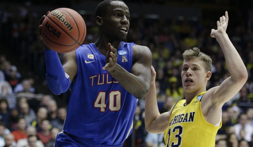 Tulsa's D'Andre Wright (40) passes against Michigan's Moritz Wagner (13) during the first half of a First Four game of the NCAA college basketball tournament, Wednesday, March 16, 2016, in Dayton, Ohio. (AP Photo/John Minchillo)