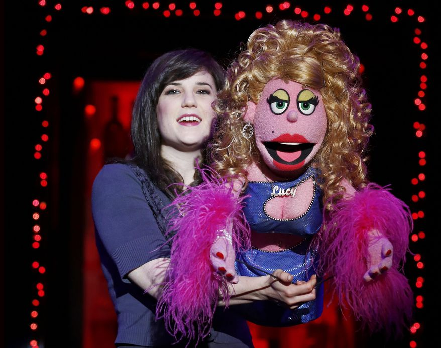 """This image released by Sam Rudy Media Relations shows puppeteer Veronica J. Kuehn, left, with Lucy from the """"Avenue Q"""" production. Puppet parties are scheduled across the country on Monday to celebrate World Puppetry Day. Professional and amateur puppeteers and their puppets are invited for the celebration in Times Square, joined by puppets from other Broadway and Off-Broadway shows past and present, including the profane monsters from """"Avenue Q."""" A huge photo will be taken to mark the event. (Carol Rosegg/Sam Rudy Media Relations via AP)"""