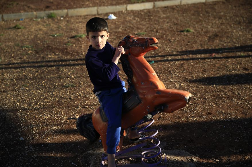 A Syrian refugee child plays at a playground at the Oncupinar camp for Syrian refugees next to the border crossing with Syria, near the town of Kilis in southeastern Turkey, Thursday, March 17, 2016. European Union leaders will push ahead Thursday with contested plans to send tens of thousands of migrants back to Turkey amid deep divisions over how to manage Europe's biggest refugee emergency in decades. Turkey hosts some 2.7 million people who have fled the five-year conflict in Syria, Turkey's neighbour to the south. (AP Photo/Lefteris Pitarakis)