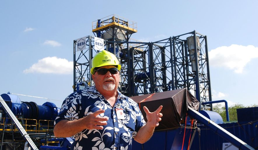 In this March 4, 2016 photo, Stan Osserman, director of the Hawaii Center for Advanced Transportation Technologies, speaks in front of a new waste to energy facility at Joint Base Pearl Harbor-Hickam, Hawaii. The Air Force unit that defends Hawaii skies will get experimental energy technology that uses trash to generate power and relies on its own small electrical grid, a system intended to keep the base operating if a bomb, cyberattack or natural disaster knocks out the local utility. (AP Photo/Audrey McAvoy)