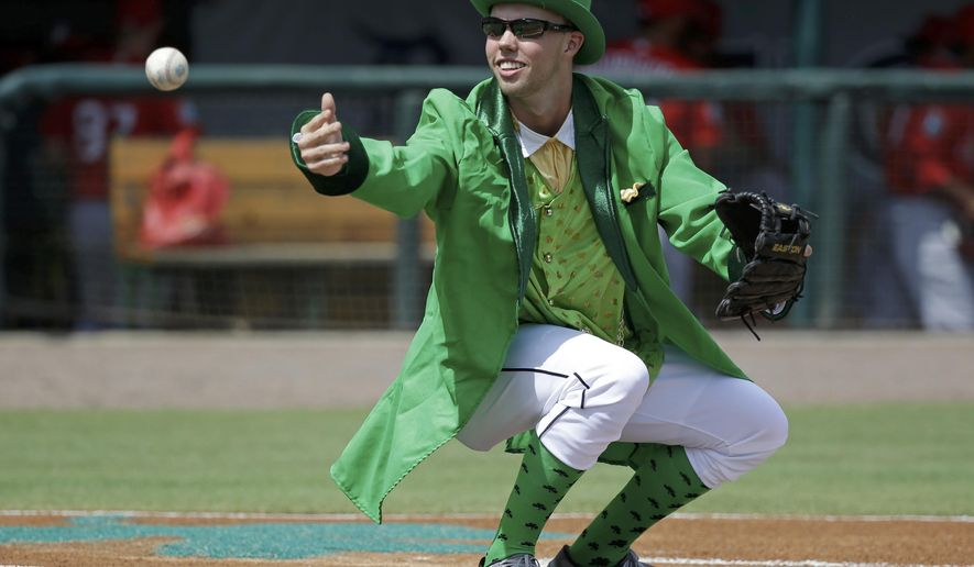 Bat boy Conner Regan dressed for St. Patrick's Day tosses a ball after catching a pitch at home plate prior to a spring training baseball game between the Detroit Tigers and the St. Louis Cardinals, Thursday, March 17, 2016, in Lakeland, Fla. (AP Photo/John Raoux)